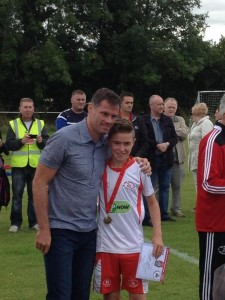 Mark Mahon receiving his medal from Jamie Carragher.